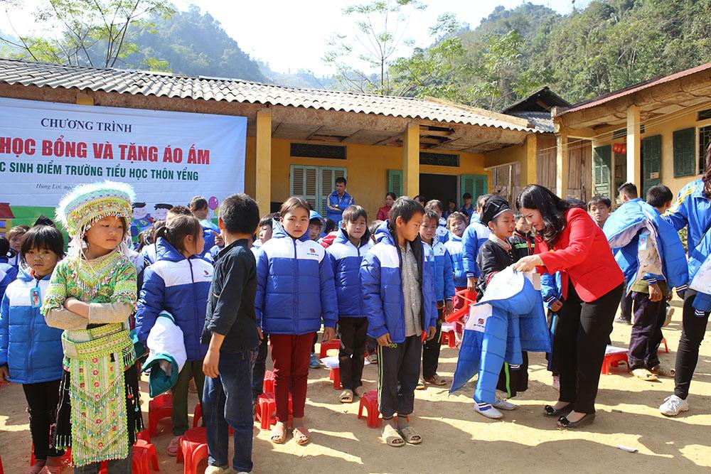 TGĐ Lê Thị Bình tự tay mặc áo ấm cho các bé tại trường Tiểu học thôn Yểng