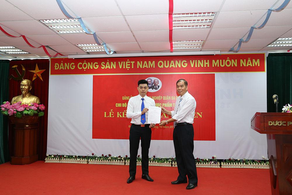 Đồng chí Nguyễn Thế Hùng, Bí thư Chi bộ Công ty TNHH Dược Phẩm Tâm Bình trao quyết định kết nạp đảng viên cho quần chúng Nguyễn Anh Đức