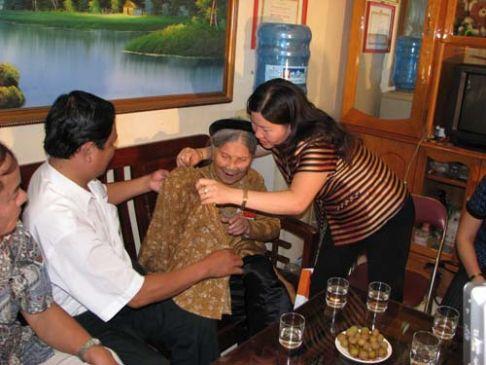 Dược sĩ Lê Thị Bình tự tay mặc áo cho Mẹ Việt Nam anh hùng Nguyễn Thị Chỉ ở Quận Ba Đình - Hà Nội