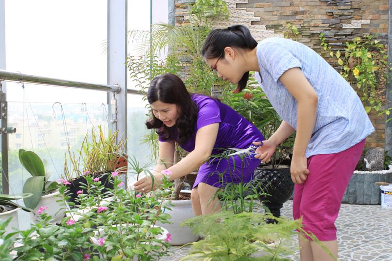 Dược sĩ Lê Thị Bình chăm sóc cây cảnh cùng con gái Bảo Châu
