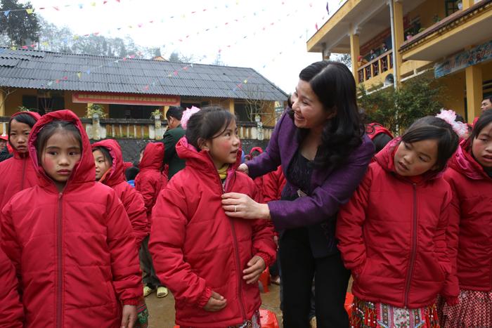Dược sĩ Lê Thị Bình mặc áo ấm cho các em học sinh tiểu học