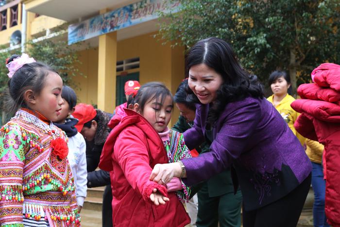 Dược sĩ Bình tận tay mặc áo ấm cho các cháu học sinh